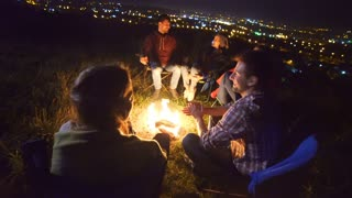 The happy people sit near the bonfire. evening night time