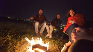 The happy people sit near the bonfire on the background of the city. night time