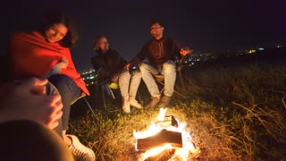 The happy people sit near the campfire. evening night time
