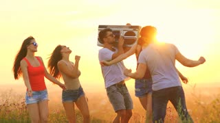 The happy people with a boom box dancing on a bright sun background. slow motion