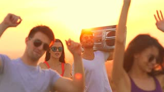 The happy people with a boom box dancing on a sun background. slow motion
