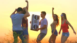 The happy people with a boom box dancing on a sunny background. slow motion