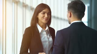 The happy woman and a man talk in the office center. slow motion