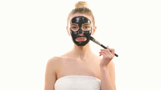 The happy woman applying a skin care black mask on the white background