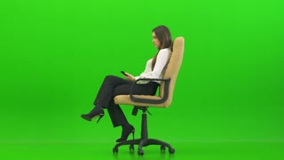 The happy woman phones on the office chair on the green background