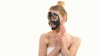 The happy woman with a black face care mask flirts on the white background