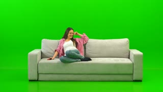 The laughing woman laying on the sofa on the green background