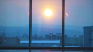 The man and a woman talking near the panoramic window on a sunrise background