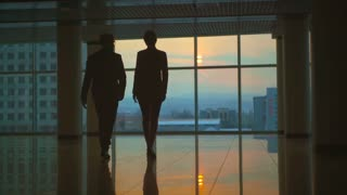 The man and a woman walking in the office hall. slow motion