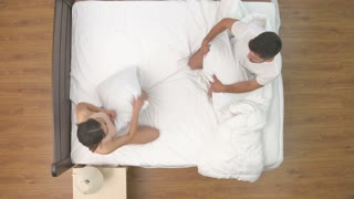 The man and woman fight with a pillow in the bed. view from above