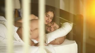 The man and woman lay on the bed over the window