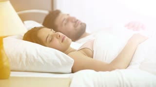 The man and woman sleeping on the bed