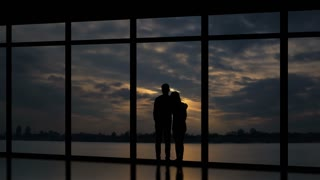 The man and woman standing near windows on a sundown background. time lapse
