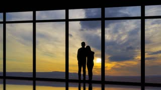 The man and woman standing near windows on a sunset background. time lapse