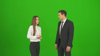The man and woman touch the virtual screen on the green background