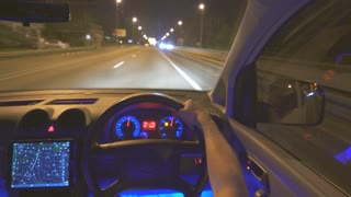 The man drive a car in the city. evening night time, left side traffic, inside view