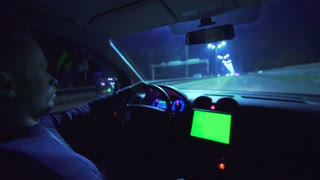 The man drive a car in the highway. inside view, green screen display on the panel. evening night time. real time capture