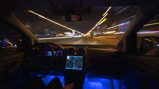 The man drive a car in the night city. Inside view. Hyperlapse. Wide angle