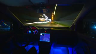 The man drive a car in the night city with a gps. Inside view. Hyperlapse. Wide angle
