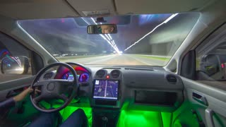 The man drive a car in the night city with a navigator. Inside view. Hyperlapse. Wide angle