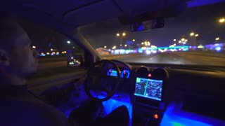 The man drive a car on the city highway evening night time. inside view, real time capture