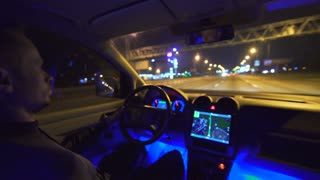 The man drive a car on the city road. evening night time. inside view. wide angle, real time capture