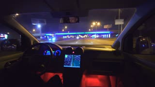 The man drive a car on the city road. inside view. evening night time, real time capture