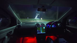 The man drive a car on the night highway. left side traffic. wide angle, real time capture