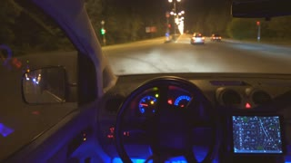 The man drive a car on the night road. inside view