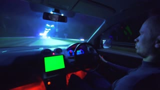 The man drive a vehicle in the night autobahn. left side traffic, wide angle, green screen display, real time capture