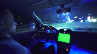 The man drive a vehicle on the night autobahn. inside view. wide angle, alpha channel green screen, real time capture