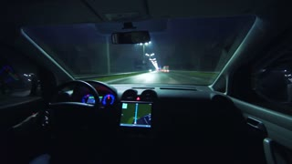 The man drive a vehicle on the night highway. inside view. wide angle, real time capture