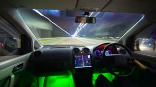 The man drive a vehicle with the green backlight. Night time. Hyperlapse. Wide angle
