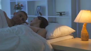The man kiss a woman on the bed. Camera around motion