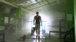The man lifting the barbell on the background of the bright light. slow motion