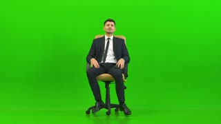 The man phones on the office chair on the green background