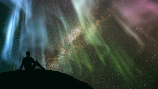 The man sitting against the star shower with a northern light. time lapse