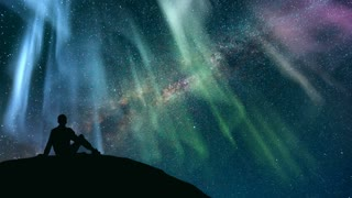 The man sitting against the starry sky with a northern light. time lapse