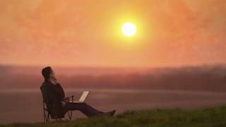 The man sitting with a laptop against the sunrise background
