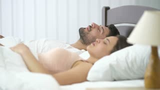 The man snore near the woman on the bed