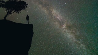 The man stand near a tree on the mountain against the meteor shower. time lapse