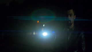 The man stand near the road with a traffic. night time. anamorphic lens shot