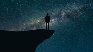 The man stand on the top of a mountain on a starry sky background. time lapse