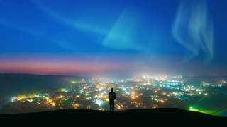 The man standing against the northern light over the night city. time lapse
