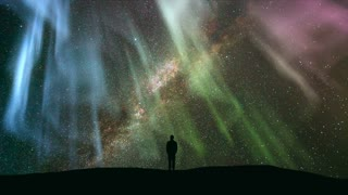 The man standing against the star shower with a northern light. time lapse