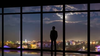 The man standing near panoramic windows on the night city background. time lapse