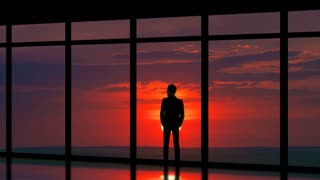 The man standing near panoramic windows on the sunset background. time lapse