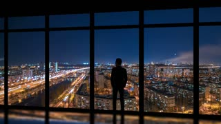 The man standing near windows on a night metropolis background. time lapse