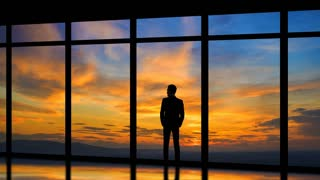 The man standing near windows on the sunrise background. time lapse