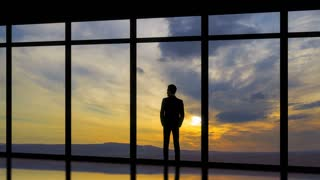 The man standing near windows on the sunset background. time lapse